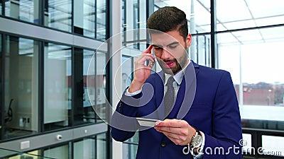 Επιχειρηματίας που χρησιμοποιεί την πιστωτική κάρτα μιλώντας στο κινητό τηλέφωνο φιλμ μικρού μήκους