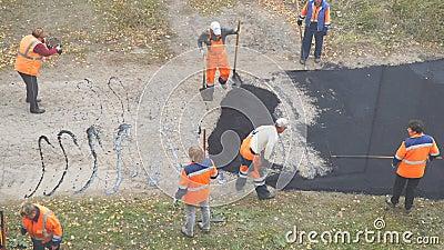 Εργάτες οικοδομών κατά τη διάρκεια του ασφαλτώνοντας δρόμου Χειρωνακτική εργασία στην κατασκευή απόθεμα βίντεο