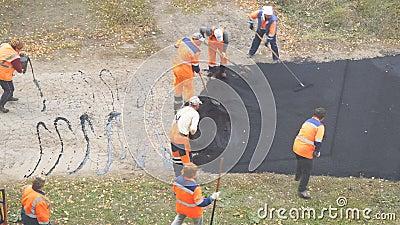 Εργάτες οικοδομών κατά τη διάρκεια του ασφαλτώνοντας δρόμου Χειρωνακτική εργασία στην κατασκευή φιλμ μικρού μήκους