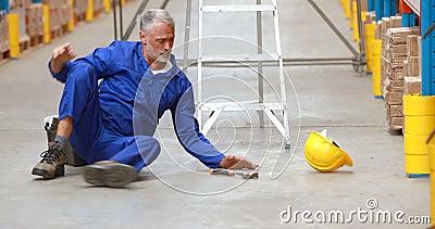 Εργαζόμενος αποθηκών εμπορευμάτων αρσενικών που πέφτει από τη σκάλα εργαζόμενος