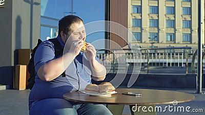 Εργαζόμενος γραφείων αρσενικών που τρώει burger για το μεσημεριανό γεύμα υπαίθρια, παχυσαρκία διατροφής άχρηστου φαγητού απόθεμα βίντεο