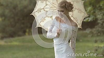 Ευγενής νύφη με μια ομπρέλα στη φύση φιλμ μικρού μήκους
