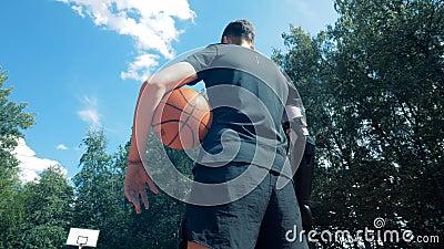 Ευρεία άποψη γωνίας ενός ατόμου με ένα τεχνητό χέρι που στέκεται σε έναν χώρο αθλήσεων με μια σφαίρα απόθεμα βίντεο