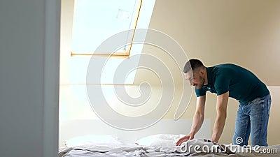 Ευτυχές άτομο που κάνει το κρεβάτι στο σπίτι απόθεμα βίντεο
