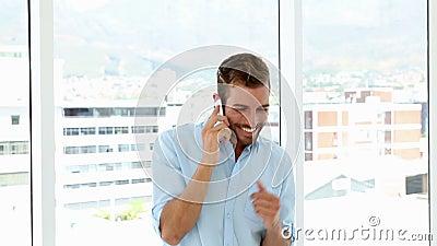 Ευτυχής επιχειρηματίας που χορεύει μετά από να πάρει τις καλές ειδήσεις απόθεμα βίντεο