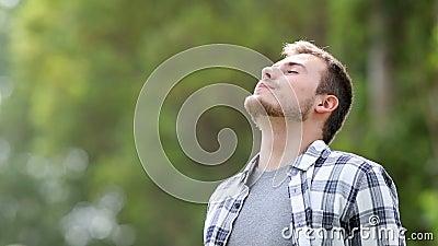 Ευτυχής νεαρός άνδρας που αναπνέει βαθιά υπαίθρια