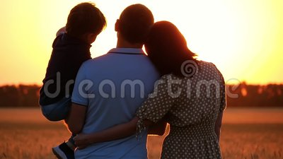 Ευτυχής οικογένεια που προσέχει το ηλιοβασίλεμα, που στέκεται σε έναν τομέα σίτου Ένα άτομο που κρατά ένα παιδί στα όπλα του Μια  απόθεμα βίντεο