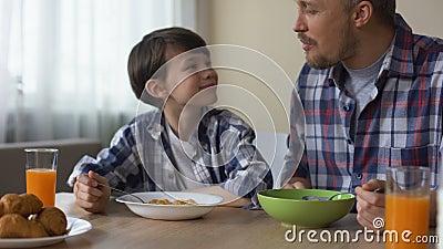 Ευτυχείς γιος και πατέρας που τρώνε τα νόστιμα δημητριακά στο πρόγευμα, παράδοση πρωινού απόθεμα βίντεο