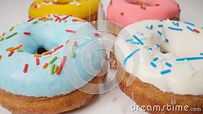Εύγευστος πολύχρωμος που βερνικώνεται donuts σε μια ομαλή κίνηση φιλμ μικρού μήκους