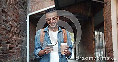 Εύθυμος νέος Άραβας σχετικά με το φλυτζάνι καφέ εκμετάλλευσης οθόνης smartphone υπαίθρια φιλμ μικρού μήκους