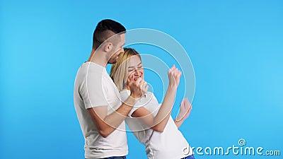 Ζευγάρι νεαρών ευτυχισμένων ανδρών και γυναικών χορεύουν μαζί στο μπλε φόντο απόθεμα βίντεο