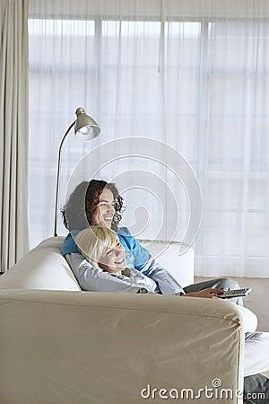 Ζεύγος στον καναπέ που προσέχει τη TV