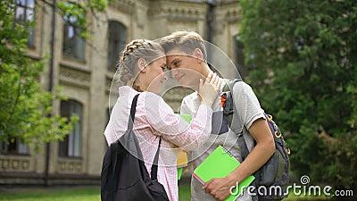 Ζεύγος του ερωτευμένου αγκαλιάσματος σπουδαστών και να σπρώξει με τη μουσούδα πριν από τις κατηγορίες, πανεπιστημιακή ζωή φιλμ μικρού μήκους