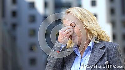 Ηλικίας θηλυκό στο κοστούμι που αισθάνεται την ένταση ματιών, ταλαιπωρία εμμηνόπαυσης, πίεση του αίματος φιλμ μικρού μήκους