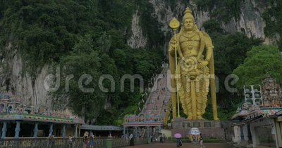 Η άποψη της εισόδου σε Batu ανασκάπτει, κλιμακοστάσιο και το χρυσό άγαλμα Murugan ενάντια στο βουνό, Gombak, Selangor, Μαλαισία απόθεμα βίντεο