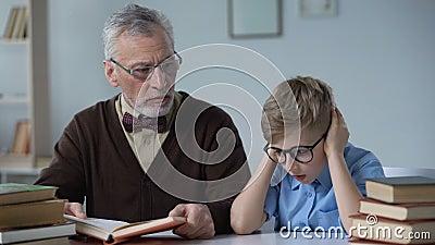 Η ανάγνωση παππούδων κρατά μεγαλοφώνως, το μικρό παιδί φαίνεται βαριεστημένο, πρόβλημα χάσματος των γενεών απόθεμα βίντεο