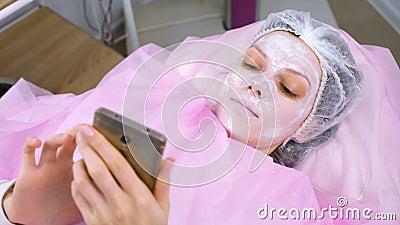 Η γυναίκα διαβάζει κάτι σε ένα κινητό τηλέφωνο ξαπλωμένη στη διαδικασία στο γραφείο του καλλυντικού με μια μάσκα στο πρόσωπό της απόθεμα βίντεο