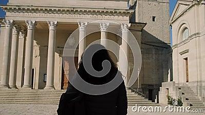 Η γυναίκα περπατά μπροστά από το Di Άγιος Μαρίνος βασιλικών απόθεμα βίντεο