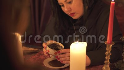 Η γυναίκα που λέει την τύχη στο σκοτεινό δωμάτιο με πολλά κεριά δίνει μια εξήγηση για το μέλλον και την πρόβλεψη της μοίρας σε μι απόθεμα βίντεο