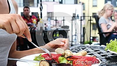 Η γυναίκα τρώει τα ψημένα στη σχάρα λαχανικά με ένα δίκρανο κοντά επάνω ενάντια στο σκηνικό των επισκεπτών απόθεμα βίντεο