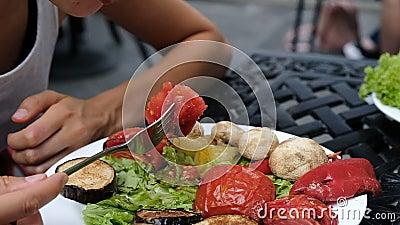 Η γυναίκα τρώει την ψημένη ντομάτα με ένα δίκρανο, ψημένη στη σχάρα κινηματογράφηση σε πρώτο πλάνο λαχανικών, σε αργή κίνηση απόθεμα βίντεο