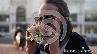 Η ελκυστική νέα γυναίκα, που χαμογελά χαρωπά, κρατά νόστιμο burger σε δύο χέρια και το τρώει Ντυμένος στην περιστασιακή εξάρτηση, απόθεμα βίντεο