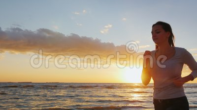 Η ελκυστική νέα γυναίκα τρέχει κατά μήκος της ακτής στο ηλιοβασίλεμα Συμμετέχετε στον αθλητισμό - υγιής τρόπος ζωής Steadicam αργ φιλμ μικρού μήκους