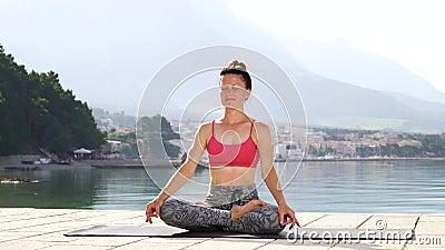 Η ενήλικη αθλητική γυναίκα meditates στο λωτό θέτει στην παραλία στην ηλιοφάνεια πρωινού απόθεμα βίντεο