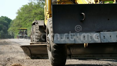 Η εργασία οδοποιίας, επισκευή μιας εθνικής οδού, το τρακτέρ ισοπεδώνει το αμμοχάλικο στο δρόμο, κάνοντας μια βάση για την τοποθέτ απόθεμα βίντεο