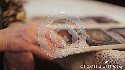 Ηλικιωμένη γυναίκα που εξετάζει μια φωτογραφία στο παλαιό λεύκωμα φωτογραφιών, μνήμες, κλίση επάνω φιλμ μικρού μήκους