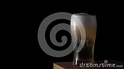 Η κρύα ελαφριά μπύρα χύνεται σε ένα γυαλί με το μαύρο υπόβαθρο μεταλλινών πτώσεων νερού πάντα, σχέδιο συνόρων Στενός επάνω μπύρας απόθεμα βίντεο