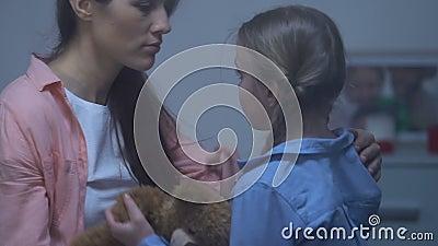 Η μητέρα που ανακουφίζει λίγη λυπημένη κόρη που κρατά teddy αντέχει, γονική υποστήριξη, προσοχή απόθεμα βίντεο