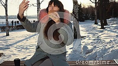 Η νέα γυναίκα τρώει burger στη χειμερινή οδό φιλμ μικρού μήκους