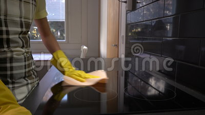 Η νοικοκυρά σκουπίζει την επιφάνεια της ηλεκτρικής σόμπας με ένα ειδικό καθαρίζοντας ύφασμα μετακινηθείτε απόθεμα βίντεο
