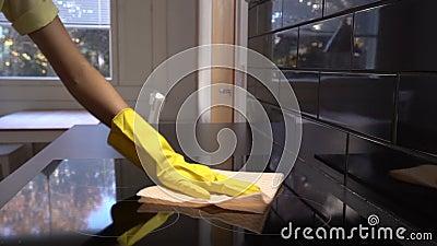 Η νοικοκυρά σκουπίζει την επιφάνεια της ηλεκτρικής σόμπας με ένα ειδικό καθαρίζοντας ύφασμα μετακινηθείτε κίνηση αργή φιλμ μικρού μήκους