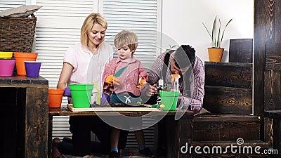 Η οικογένεια κάθεται με τα λουλούδια της Μικρότερα και χόμπι, η οικογένεια καλλιεργεί λουλούδια μαζί Ομορφιά και φύση Σπίτι για χ απόθεμα βίντεο