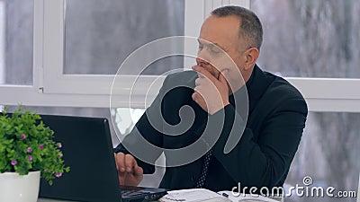 Η παλαιά εργασία επιχειρηματιών με το φορητό προσωπικό υπολογιστή και παίρνει τις σημειώσεις στο σημειωματάριο στην αρχή φιλμ μικρού μήκους
