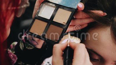 Η στυλίστας βάζει σκόνη στο μέτωπο της κοπέλας Διαδικασία μακιγιάζ απόθεμα βίντεο
