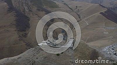 Η Aerial γύρω από την προσγείωση βλέπει την αρχαία γεωργιανή εκκλησία στα υψίπεδα στο βουνό Kazbek απόθεμα βίντεο