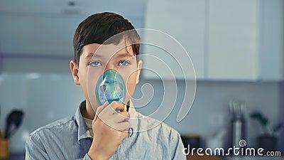 Θεραπεία του άσθματος, το αγόρι εισπνέει µέσω εισπνοής Στέκομαι στην κουζίνα απόθεμα βίντεο