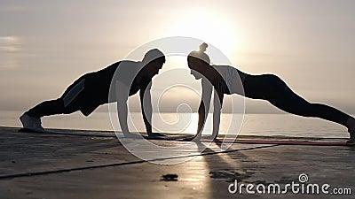 Θετικά αθλητικά υψηλά fives ζευγών ασκώντας έξω στο μέτωπο τη θάλασσα Ο εύθυμος άνδρας και η κατάλληλη γυναίκα χτυπούν ενώ απόθεμα βίντεο