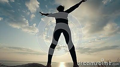Θηλυκή σκιαγραφία που κάνει τη σωματική άσκηση ενάντια στην ανατολή απόθεμα βίντεο