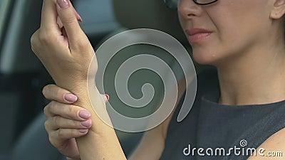 Θηλυκός θερμαίνοντας καρπός μετά από τη βαριά ημέρα εργασίας, που κάθεται στο αυτοκίνητο, μόνος-μασάζ απόθεμα βίντεο
