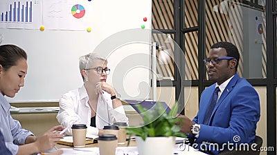 Θηλυκός οικονομικός εκτελεστικός και αφρικανικός διευθυντής που συζητά τους στόχους προγράμματος με την πολυφυλετική ομάδα απόθεμα βίντεο