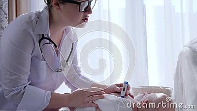 Ιατρικός εξετάζει, γιατρός με τη θερμοκρασία μέτρων θερμομέτρων του νεογέννητου σώματος στο ελαφρύ δωμάτιο απόθεμα βίντεο