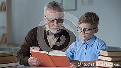 Ιστορία περιπέτειας ανάγνωσης Grandpa μεγαλοφώνως σε λίγο εγγονό, την οικογενειακή προσοχή και τη ζεστασιά απόθεμα βίντεο