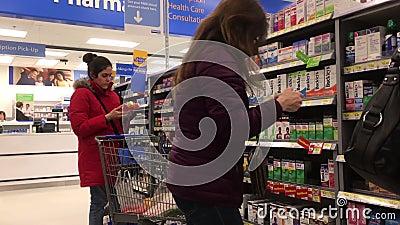 Κίνηση ατόμων που αγοράζουν φάρμακα στο φαρμακείο μέσα στο κατάστημα της Walmart απόθεμα βίντεο