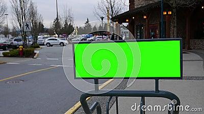 Κίνηση πράσινης αφίσας για την αγγελία σας με θολωμένους ανθρώπους που περπατούν δίπλα στο πάρκινγκ φιλμ μικρού μήκους