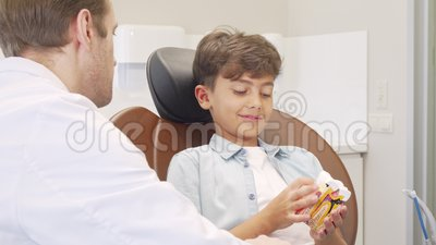 Καλός επισκεπτόμενος οδοντίατρος μικρών παιδιών για την εξέταση δοντιών απόθεμα βίντεο