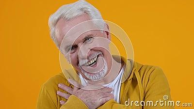 Καλός συνταξιούχος θαυμαζόμενος σε πορτοκαλί φόντο, κοιτάζοντας με αγάπη, καλά νέα απόθεμα βίντεο